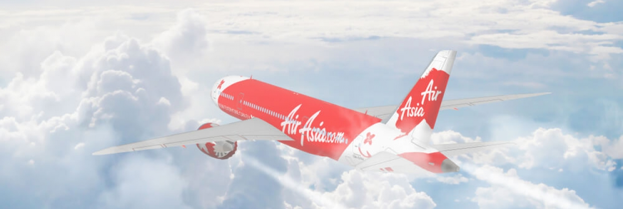 Aerial view of Air Asia cruising above Fluffy White Clouds