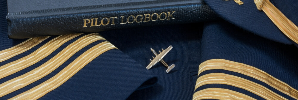 Pilot logbook with a captains hat and shoulder sleeves with four