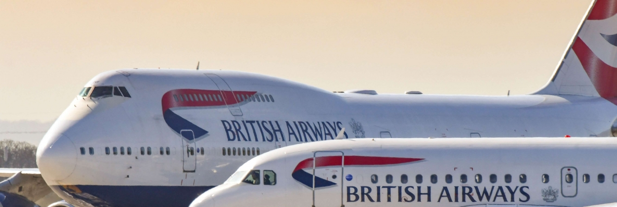 British Airways Airbus A319 jet taxiing past one of the airline's