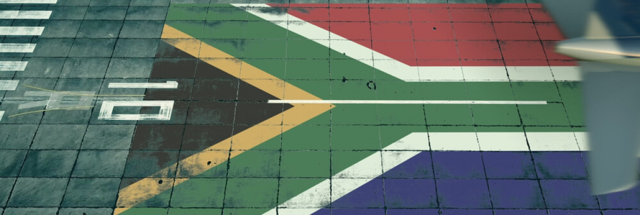 Aerial view of a landing airliner and flag of South Africa on the