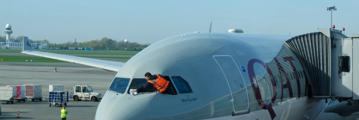 Worker is cleaning Qatar Airways plane front window before depart
