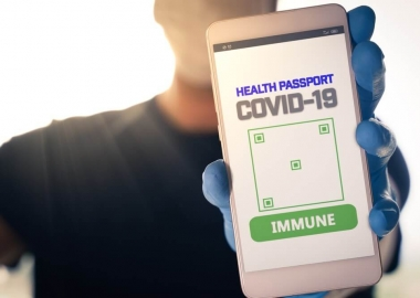 Man holding a smartphone with Immune digital passport for Covid-1