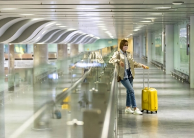 Woman with luggage stuck at empty airport terminal